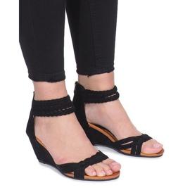 Svarta sandaler på en delikat Desun-kil